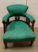 A mahogany upholstered library tub arm chair on turned legs ending in brass castors