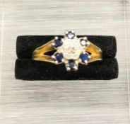 An 18 ct yellow gold Daisy style ring with central diamond and six sapphires (4.2g)