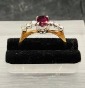 A 14 ct yellow gold ring with central ruby and three small diamonds to either side.