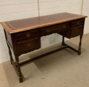 A leather topped writing desk on turned legs (H77cm W129cm D57cm)