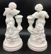 A Pair of Franklin Mint Cherub candlesticks