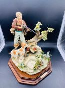 A Capodimonte figure of a hunter and dog with a duck
