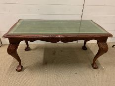 A glass topped coffee table on ball and claw feet (H45cm W97cm D50cm)