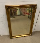 A gilt framed mirror with scrolling swags to corners