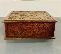 A Chinese carved box with grapes and vines to side.