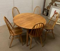 A blonde Ercol dining table of oval design and five chairs 120cm Dia x 73cm H