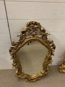A gilt wall mirror with shaped mirror plate and scrolls (78cm x 43cm)
