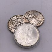 A selection of three American silver dollars.