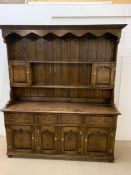 A large oak dresser, with plate rack and small cupboards sat on a base with drawers and cupboards (