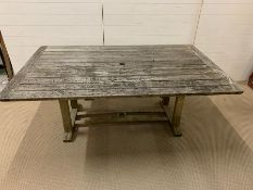 A large weathered wooden slatted garden table (W183cm D112cm)