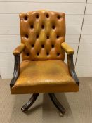A leather button back office chair on castors
