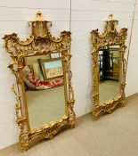 A pair of Italian giltwood wall mirrors, the shaped is a rectangular plate within a profusely carved
