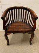 A Indian hardwood horse shoe armchair, the curved arms with scrolled arms