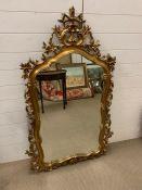 A gilt wall mirror with scroll carved frame (143cm x 80cm)