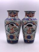 A pair of Amari vases, decorated with figures to sides