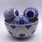 Four blue and white ceramic balls and a bowl