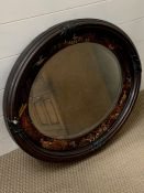 An oval mirror with hand painted frame depicting an oriental scene.