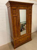 A Large Walnut veneered wardrobe with single mirrored door and large drawer on bracket feet (W 125