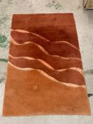 A hand knotted and made in Nepal red and orange rug with wave design through centre (178cm x 120cm)
