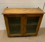 A antique pine wall hanging display case with two glazed doors to front (H67cm W74cm D23cm)
