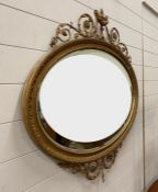 A George IV style giltwood over mantle mirror surmounted by an urn with swags and finials