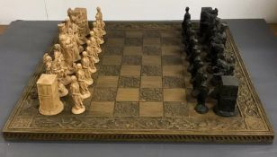 A chess board and large carved pieces