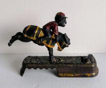 A late Victorian cast metal comical jockey money box, possible maker of J E Stevens, embossed