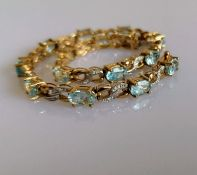 An aquamarine line or tennis bracelet with diamond decoration on 9ct yellow gold, each stone 4mm x