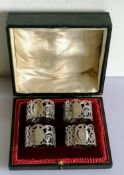 A George V cased set of four silver napkin rings with pierced decoration, numbered, hallmarked and