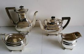 An Edwardian four-piece silver tea and coffee service with fruitwood harp handles, leaf scroll
