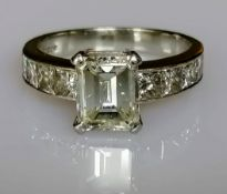 A diamond ring set with a central emerald-cut diamond, weighing a calculated 2.00 carat