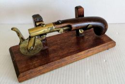 A 19th century eprouvette or gunpowder tester, the mahogany pistol grip with brass barrel, touch