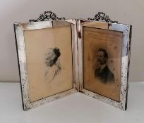 An Edwardian silver double photo frame with applied scroll pediment decoration by E Mander & Son,