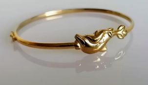 A yellow gold bangle with dolphin decoration, stamped 9kt, 4.33g
