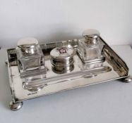 A George V silver ink stand with twin squared-based ink bottles, pierced gallery, enamelled