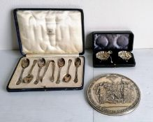 A George V cased set of six silver coffee spoons and tongs with rococo decoration to terminals by