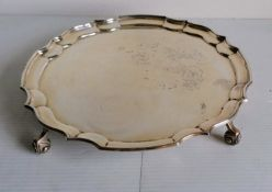A Georgian-style silver salver with pie crust decoration on four leaf scroll feet by Sanders &