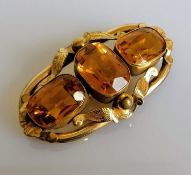 A Victorian three-stone citrine brooch on an elliptical gold frame with etched foliate decoration,