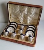 A cased set of six Edwardian Coalport floral and gilt-edged coffee cans and saucer with pierced