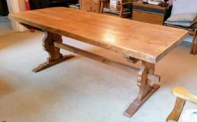 A hardwood Arts & Crafts-style refectory dining table with carved trestle supports, 75 x 200 x 79 cm