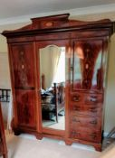 An Edwardian bedroom suite comprising: a treble wardrobe with carved pediment, interior fitted for