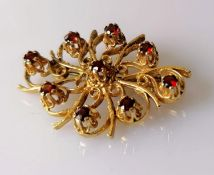 An oval 9ct yellow gold filigree brooch decorated with nine garnets, hallmarked, 30mm x 40mm, 9.18g
