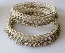 Two Indian silver anklets or bangles with tassels, each 10 cm diameter, 316g