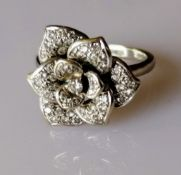 An 18ct white gold nine-petal diamond encrusted flower ring, the central diamond 0.05 carats