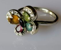 An 18ct white gold multi-gem flower ring with diamond decoration, size L, hallmarked, 4.79g