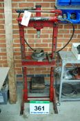 An Unbranded Manual Hydraulic Bearing Press with a Wall Mounted Lin Bin Rack Containing Accessories