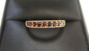 9ct yellow imported gold band ring set with 10 round cut natural garnets Approx 1.5 grams gross,