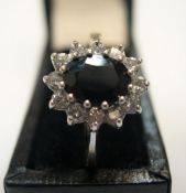 9ct yellow gold dress ring with large central sapphire surrounded by CZ Approx 2.4 grams gross