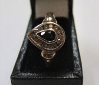 9ct yellow gold ring with pear cut sapphire surrounded by white stones. Approx 1.5 grams gross, size