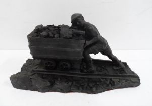 Made from British coal is this figure of a Man pushing a small coal cart,